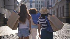 Vue arrière des femmes mettant des sacs en papier sur l'épaule banque de vidéos