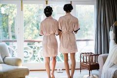 Vue arrière des femmes tenant la fenêtre proche Image stock