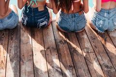 Vue arrière des filles assez jeunes s'asseyant à la piscine Photo stock
