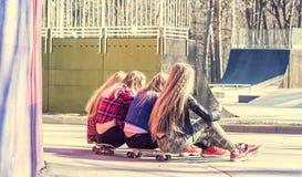 Vue arrière des filles s'asseyant sur des longboards dans le skatepark Photographie stock