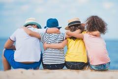 vue arrière des garçons et des filles s'asseyant ensemble sur le tronc en bois au bord de la mer Photographie stock libre de droits