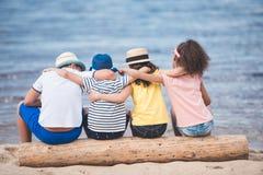 vue arrière des garçons et des filles s'asseyant ensemble sur le tronc en bois au bord de la mer Images libres de droits