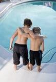 Vue arrière des garçons regardant dans la piscine Photos libres de droits