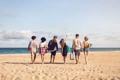 Vue arrière des jeunes hommes et de la femme sur le bord de mer Photographie stock