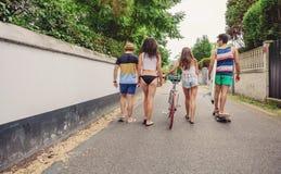 Vue arrière des jeunes marchant le long de la route Photographie stock
