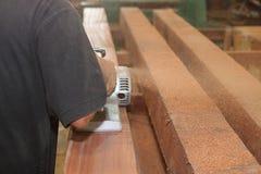 Vue arrière des mains du charpentier à l'aide de la planeuse électrique avec la planche en bois dans l'atelier de menuiserie avec Images stock
