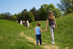 Vue arrière des mains et de la marche d'And Sister Holding de frère par le parc chez Sunny Spring Day Photos stock