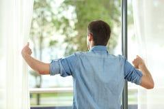 Vue arrière des rideaux et du regard en ouverture de l'homme loin image libre de droits