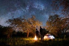 Vue arrière des touristes romantiques de couples se tenant à un feu de camp, à un beau ciel nocturne complètement des étoiles et  Photos stock