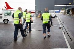 Vue arrière des travailleurs de sexe masculin marchant sur la piste humide photos stock