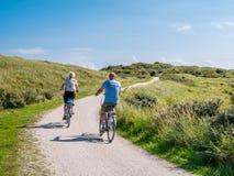 Vue arrière des vélos de monte de personnes sur le chemin de bicyclette en dunes de Het Oerd de réserve naturelle sur l'île occid photographie stock