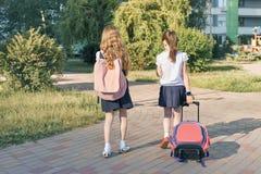 Vue arrière, deux écolières de petites filles allant instruire avec des sacs à dos image stock