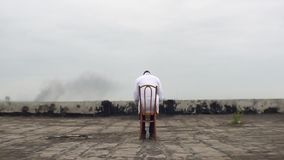 Vue arrière du docteur africain inconnu s'asseyant sur la chaise avec le livre Il se repose sur le dessus de toit de banque de vidéos