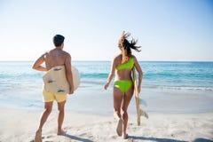 Vue arrière du fonctionnement de couples tout en tenant des planches de surf à la plage Images stock