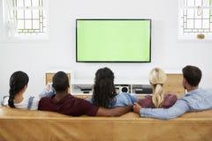 Vue arrière du groupe de jeunes amis regardant la télévision ensemble Images stock