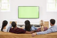 Vue arrière du groupe de jeunes amis regardant la télévision ensemble Photo libre de droits