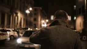 Vue arrière du jeune homme élégant marchant par la ruelle abandonnée seule et pensant le soir banque de vidéos