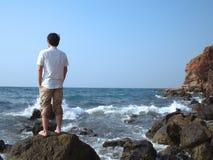 Vue arrière du jeune homme asiatique seul songeur se tenant sur la roche du bord de la mer photos stock