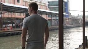 Vue arrière du jeune homme de touristes attendant le taxi de bateau au pilier local à Bangkok banque de vidéos