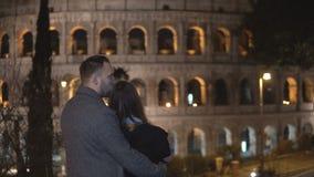 Vue arrière du jeune homme et de la femme se tenant près du Colosseum à Rome, Italie et étreignant ensemble Photos libres de droits
