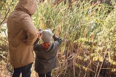 vue arrière du père et du fils regardant par des jumelles tout en se tenant ensemble images stock