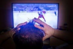Vue arrière du sport de observation principal masculin dans la TV photos stock
