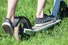 Vue arrière en gros plan du scooter de coup-de-pied d'équitation d'enfant, herbe verte sur le pré d'été Photo stock