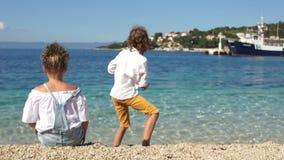 Vue arrière, garçon bouclé et fille jouant avec des cailloux sur les rivages du méditerranéen L'Adriatique, Croatie, Dolmatia banque de vidéos