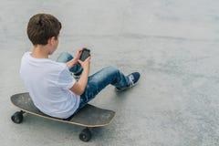 Vue arrière L'adolescent s'assied sur la planche à roulettes, utilise le smartphone, instrument numérique, jeux d'ordinateur de j photo libre de droits