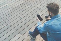 Vue arrière L'homme de hippie s'assied sur le banc dehors, boit du café et utilise le smartphone Le type dans la chemise de denim images stock