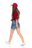 Vue arrière latérale de marche de femme occasionnelle d'isolement Image stock