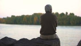 Vue arrière se reposante de berge de grand-père triste, solitude de vieillesse, repos paisible banque de vidéos