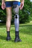 Vue arrière sur la jambe fausse de l'homme se tenant sur l'herbe Photographie stock libre de droits