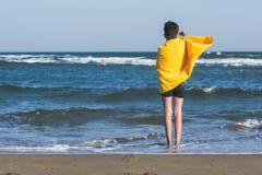 Vue arrière sur la position de garçon sur le bord de la mer de la plage dans la serviette jaune et regarder sur la mer Concept photographie stock libre de droits