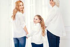 Vue arrière sur trois dames tournant des têtes à l'appareil-photo Photo stock