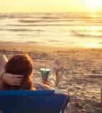 Vue arrière sur une femme appréciant le coucher du soleil avec le cocktail en Albanie à la côte arénacée de Mer Adriatique Image libre de droits