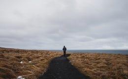 Vue arrière un homme seul marchant sur le sentier piéton dans le domaine sec photographie stock libre de droits