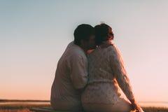 Vue arrière un ménage marié une silhouette se reposant sur un banc Photographie stock