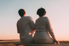 Vue arrière un ménage marié une silhouette se reposant sur un banc Photo stock