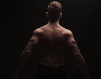 Vue arrière d'homme musculaire fléchissant son dos et bras Photos libres de droits