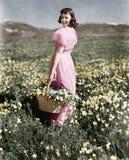 Vue arrière d'une fille se tenant dans un pré tenant un panier de fleur et sourire (toutes les personnes représentées ne sont pas Image stock