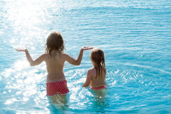 Vue arrière de filles d'enfants dans la plage au coucher du soleil Photographie stock