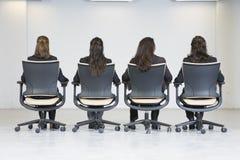 Vue arrière de quatre femmes d'affaires s'asseyant sur le bureau Photographie stock libre de droits