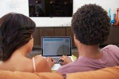 Vue arrière des couples utilisant des opérations bancaires en ligne sur l'ordinateur portable Photos libres de droits