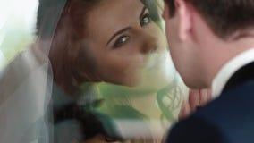 Vue au-dessus d'épaule de marié à la belle jeune mariée attirante de brune avec le maquillage naturel in camera et puis regardant banque de vidéos