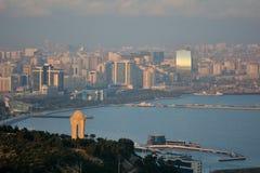 Vue au-dessus de Bakou et de la Mer Caspienne, en soleil avec la brume montrant le monument du 20 janvier dans le premier plan Images stock