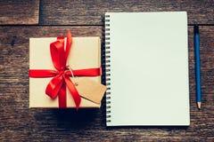 Vue au-dessus de boîte-cadeau et de carnet bruns avec l'étiquette sur le backgrou en bois Image libre de droits