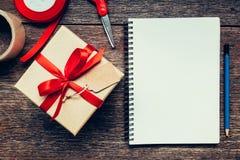 Vue au-dessus de boîte-cadeau et de carnet bruns avec l'étiquette sur le backgrou en bois Image stock