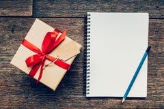 Vue au-dessus de boîte-cadeau et de carnet bruns avec l'étiquette sur le backgrou en bois Images libres de droits