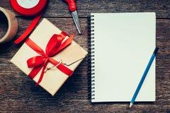 Vue au-dessus de boîte-cadeau et de carnet bruns avec l'étiquette sur le backgrou en bois Photos libres de droits